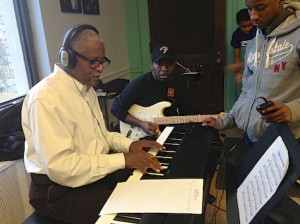 Howard Sandifer, left, guitar instructor Wilbert Crosby, center, work with students at the CWCMC 2