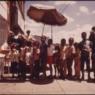 800px-GHETTO_BLACK_CHILDREN_LINE_UP_FOR_SNOW_CONES_FROM_A_SIDEWALK_VENDOR_ON_CHICAGO'S_WEST_SIDE_IN_THE_SUMMER_OF_1973...._-_NARA_-_556212